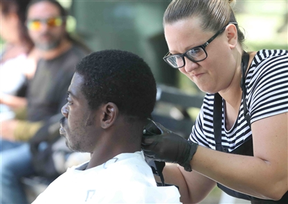 Charlene Minx and Julie Jackson cut hair for free for men and women that are either homeless or down on their luck at Fireman's Park in Buffalo on Sunday, June 17, 2018.