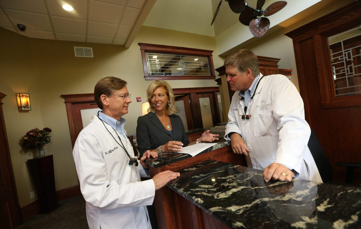 Westermeier Martin Dental Care partners Dr. Jeff Martin, left, and R. Scott Westermeier, right, talk with Maria Miecyjak, the practice administrator, on Aug. 4, 2015. (Sharon Cantillon/News file photo)