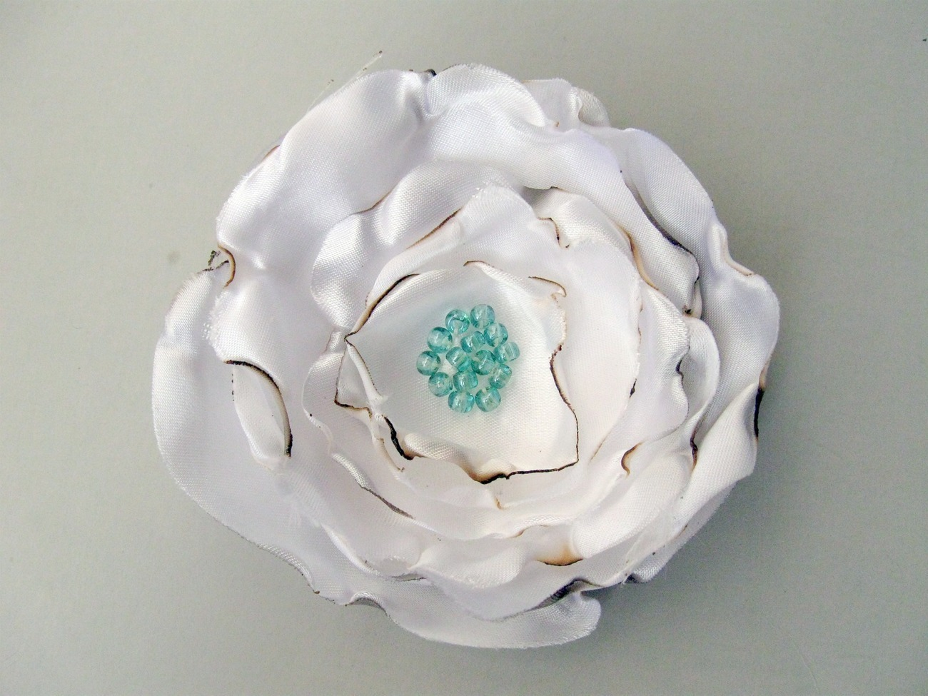 Handmade antiqued white satin flower. Aquamarine blue beads.