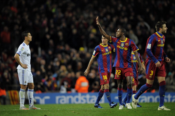 BARCELONA, SPAIN - NOVEMBER 29:  Cristiano Ronaldo of Real Madrid (L) looks on as Eric Abidal (2ndR) of Barcelona gestures after Barcelona  scored five goals againts Real Madrid, during the La Liga match between Barcelona and Real Madrid at the Camp Nou Stadium on November 29, 2010 in Barcelona, Spain.  (Photo by David Ramos/Getty Images)