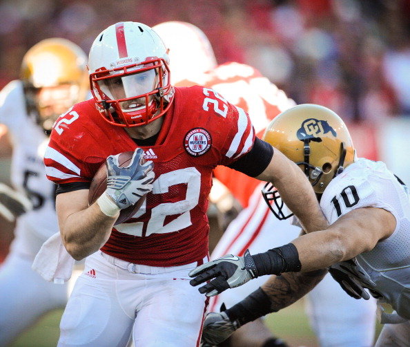LINCOLN, NE - NOVEMBER 26: Rex Burkhead #22 of the Nebraska Cornhuskers runs past Michael Sipili #10 of the Colorado Buffaloes during the first half of their game at Memorial Stadium on November 26, 2010 in Lincoln, Nebraska.  (Photo by Eric Francis/Getty Images)