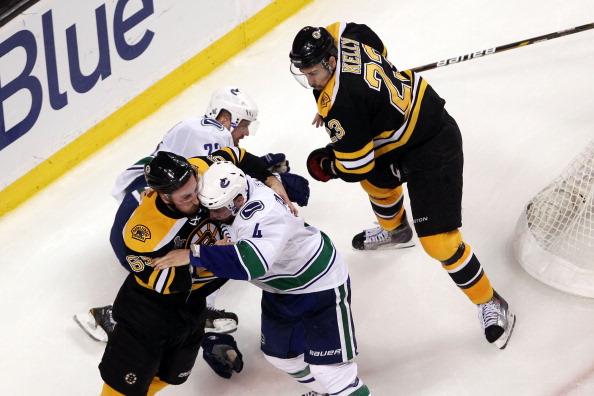 BOSTON, MA - JUNE 08:  Brad Marchand #63 of the Boston Bruins fights with Keith Ballard #4 of the Vancouver Canucks after he dodged Daniel Sedin #22 of the Vancouver Canucks during Game Four of the 2011 NHL Stanley Cup Final at TD Garden on June 8, 2011 in Boston, Massachusetts.  (Photo by Jim Rogash/Getty Images)