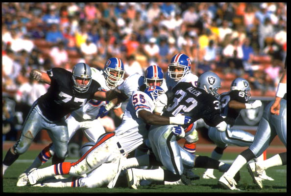 4 DEC 1988:  LOS ANGELES RAIDERS RUNNING BACK MARCUS ALLEN IS TACKLED BY DENVER BRONCOS LINEBACKER MICHAEL BROOKS IN 21-20 VICTORY OVER THE DENVER BRONCOS AT THE LOS ANGELES MEMORIAL COLISEUM IN LOS ANGELES, CALIFORNIA.