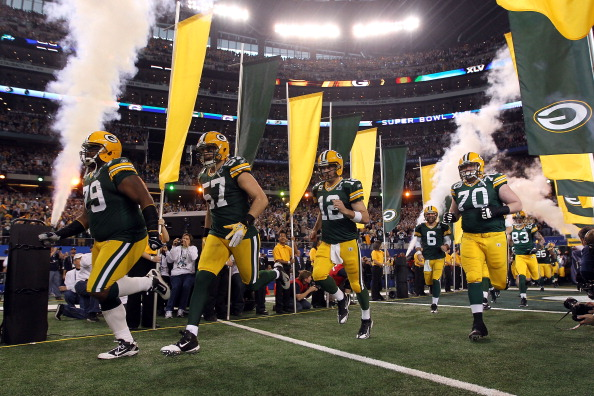 ARLINGTON, TX - FEBRUARY 06:  Ryan Pickett #79, Matt Wilhelm #57, Aaron Rodgers #12 and T.J. Lang #70 of the Green Bay Packers runs out of the tunnel to take on the Pittsburgh Steelers during Super Bowl XLV at Cowboys Stadium on February 6, 2011 in Arlington, Texas.  (Photo by Doug Pensinger/Getty Images)