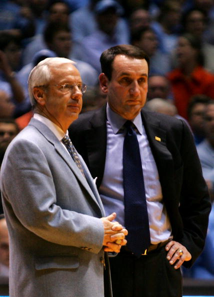 CHAPEL HILL, NC - MARCH 04:  Head coach Mike Krzyzewski (R) of the Duke Blue Devils waits on the officials with head coach Roy Williams of the University of North Carolina Tar Heels after an incident involving Tyler Hansbrough and Gerald Henderson during their game at the Dean E. Smith Center on March 4, 2007 in Chapel Hill, North Carolina. North Carolina defeated Duke, 86 - 72.  (Photo by Streeter Lecka/Getty Images)