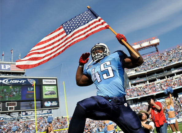NASHVILLE, TN - NOVEMBER 21:  Ahmard Hall #45 of the Tennessee Titans, an armed services veteran, brings out the American flag before a game against the Washington Redskins at LP Field on November 21, 2010 in Nashville, Tennessee.  (Photo by Grant Halverson/Getty Images)