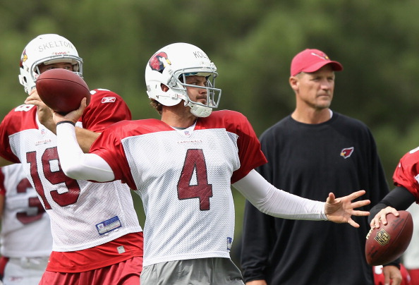 FLAGSTAFF, AZ - AUGUST 04:  Quarterback Kevin Kolb #4 of the Arizona Cardinals throws a pass as head coach  Ken Whisenhunt watches during the team training camp at Northern Arizona University on August 4, 2011 in Flagstaff, Arizona.  (Photo by Christian Petersen/Getty Images)
