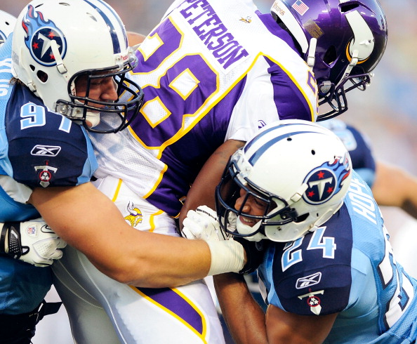 NASHVILLE, TN - AUGUST 13:  Karl Klug #97 and Chris Hope #24 of the Tennessee Titans tackle Adrian Peterson #28 of the Minnesota Vikings during a preseason exhibition game at LP Field on August 13, 2011 in Nashville, Tennessee.  (Photo by Grant Halverson/Getty Images)