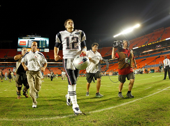 MIAMI GARDENS, FL - SEPTEMBER 12:   Tom Brady #12 of the New England Patriots jogs off the field after winning a game against the Miami Dolphins at Sun Life Stadium on September 12, 2011 in Miami Gardens, Florida.  (Photo by Mike Ehrmann/Getty Images)