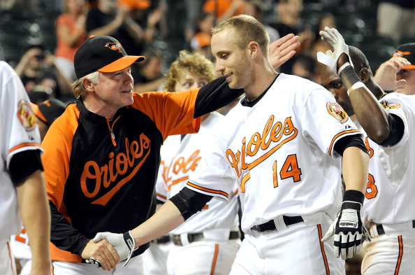 BALTIMORE, MD - AUGUST 10:  Nolan Reimold #14 of the Baltimore Orioles celebrates with manager Buck Showalter #26 after hitting the game winning home run in the tenth inning against the Chicago White Sox at Oriole Park at Camden Yards on August 10, 2011 in Baltimore, Maryland. The Orioles won the game 6-4.  (Photo by Greg Fiume/Getty Images)