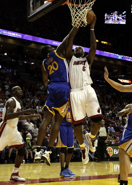 MIAMI, FL - JANUARY 01:  Forward LeBron James #6 of the Miami Heat scores againts forward Ekpe Udoh #20 of the Golden State Warriors at American Airlines Arena on January 1, 2011 in Miami, Florida.  NOTE TO USER: User expressly acknowledges and agrees that, by downloading and/or using this Photograph, User is consenting to the terms and conditions of the Getty Images License Agreement.  (Photo by Marc Serota/Getty Images)