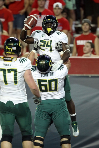 TUCSON, AZ - SEPTEMBER 24:  Runningback Kenjon Barner #24 of the Oregon Ducks is hoisted up by Ryan Clanton #60 after scoring on a 6 yard rushing touchdown against the Arizona Wildcats during the second quarter of the college football game at Arizona Stadium on September 24, 2011 in Tucson, Arizona.  The Ducks defeated the Wildcats 56-31. (Photo by Christian Petersen/Getty Images)