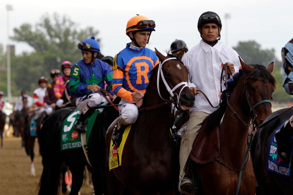 LOUISVILLE, KY - MAY 07:  Jockey Ramon A. Dominguez, riding Stay Thirsty #4, is escourted onto the track by an outrider for the running of the 137th Kentucky Derby at Churchill Downs on May 7, 2011 in Louisville, Kentucky.  (Photo by Rob Carr/Getty Images)
