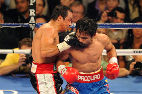 LAS VEGAS, NV - NOVEMBER 12:  (L-R) Juan Manuel Marquez connects with a right to the face of Manny Pacquiao during the WBO world welterweight title fight at the MGM Grand Garden Arena on November 12, 2011 in Las Vegas, Nevada.  (Photo by Ethan Miller/Getty Images)