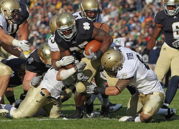 SOUTH BEND, IN - OCTOBER 29: Jonas Gray #25 of the Notre Dame Fighting Irish is hit by (L-R) Caleb King #57, Chris Ferguson #23 and Wave Ryder #8 of the Navy Midshipmen at Notre Dame Stadium on October 29, 2011 in South Bend, Indiana. (Photo by Jonathan Daniel/Getty Images)
