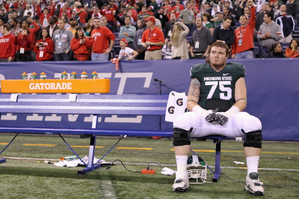 INDIANAPOLIS, IN - DECEMBER 03:  Jared McGaha #75 of the Michigan State Spartans sits alone on the bench dejected after they lost 42-39 against the Wisconsin Badgers during the Big 10 Conference Championship Game at Lucas Oil Stadium on December 3, 2011 in Indianapolis, Indiana.  (Photo by Andy Lyons/Getty Images)