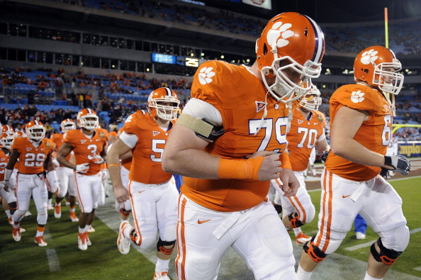 CHARLOTTE, NC - DECEMBER 03:  The Clemson Tigers take the field for warm ups led by Phillip Price #79 prior to the ACC Championship game against the Virginia Tech Hokies at Bank of America Stadium on December 3, 2011 in Charlotte, North Carolina.  (Photo by Jared C. Tilton/Getty Images)