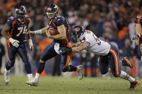 DENVER, CO - DECEMBER 11:  Quarterback Tim Tebow #15 of the Denver Broncos tries to break a tackle by linebacker Brian Urlacher #54 of the Chicago Bears as he scrambles during the overtime period at Sports Authority Field at Mile High on December 11, 2011 in Denver, Colorado. The Broncos defeated the Bears 13-10.  (Photo by Doug Pensinger/Getty Images)