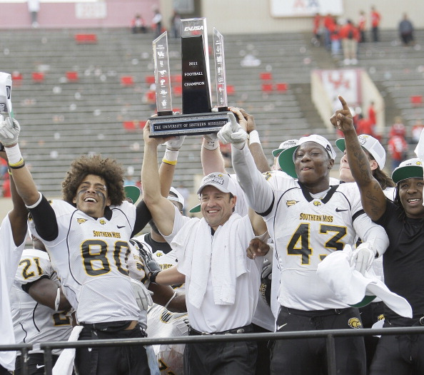 HOUSTON - DECEMBER 03:  Head coach Larry Fedora of the Southern Miss Golden Eagles holds up the Conference USA trophy with Ryan Balentine #80 and Tim Green #43 after defeating the Houston Cougars 49-28 at Robertson Stadium on December 3, 2011 in Houston, Texas.  (Photo by Bob Levey/Getty Images)