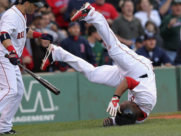 BOSTON, MA - SEPTEMBER 17:  Carl Crawford #13 of the Boston Red Sox tumbles after scoring a run at home as teammate Marco Scutaro #10 of the Boston Red Sox watches during a game with the Tampa Bay Rays in the third inning at Fenway Park September 17, 2011 in Boston, Massachusetts. (Photo by Jim Rogash/Getty Images)