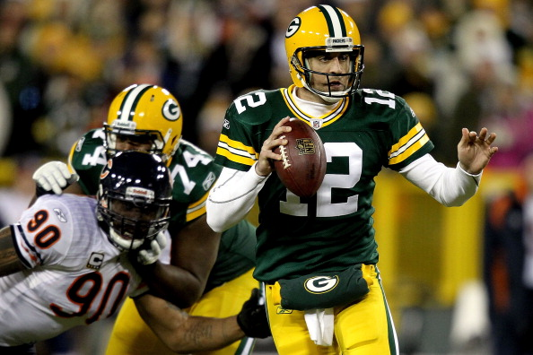 GREEN BAY, WI - DECEMBER 25: Quarterback Aaron Rodgers #12 of the Green Bay Packers is chased out of the pocket while playing the Chicago Bears at Lambeau Field on December 25, 2011 in Green Bay, Wisconsin.  (Photo by Matthew Stockman/Getty Images)