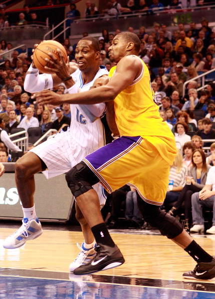 ORLANDO, FL - FEBRUARY 13:  Dwight Howard #12 of the Orlando Magic drives against Andrew Bynum #17 of the Los Angeles Lakers during the game at Amway Arena on February 13, 2011 in Orlando, Florida.  NOTE TO USER: User expressly acknowledges and agrees that, by downloading and or using this Photograph, user is consenting to the terms and conditions of the Getty Images License Agreement.  (Photo by Sam Greenwood/Getty Images)