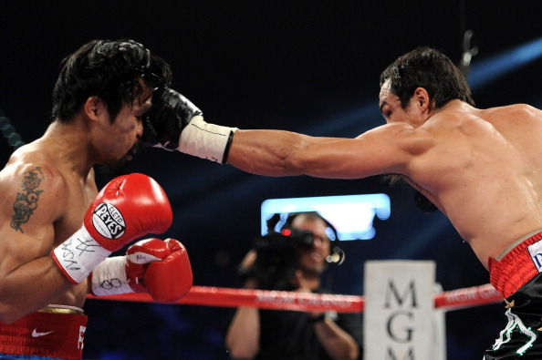 LAS VEGAS, NV - NOVEMBER 12:  (R-L) Juan Manuel Marquez throws a left to the head of Manny Pacquiao during the WBO world welterweight title fight at the MGM Grand Garden Arena on November 12, 2011 in Las Vegas, Nevada.  (Photo by Harry How/Getty Images)