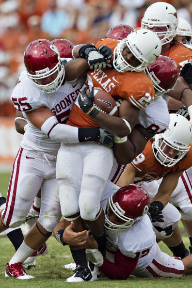 DALLAS, TX - OCTOBER 8:   Malcolm Brown #28 of the Texas Longhorns is tackled by the defense of the Oklahoma Sooners at the Cotton Bowl on October 8, 2011 in Dallas, Texas.  The Sooners defeated the Longhorns 55 to 17.  (Photo by Wesley Hitt/Getty Images)