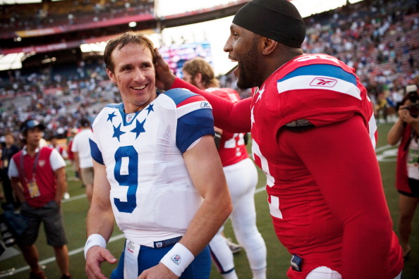 HONOLULU - JANUARY 30:  Drew Brees, #9 of the New Orleans Saints, shares a laugh with Devin McCourty, #32 of the New England Patriots, after the 2011 NFL Pro Bowl at Aloha Stadium on January 30, 2011 in Honolulu, Hawaii. NFC won 55-41 over the AFC. (Photo by Kent Nishimura/Getty Images)
