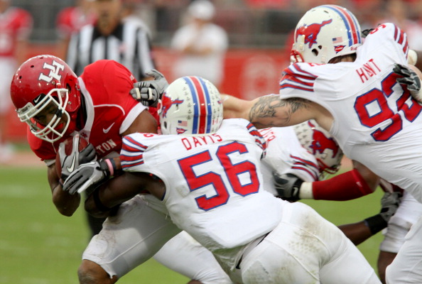 HOUSTON, TX - NOVEMBER 19: Running back Charles Simms #5 of the Houston Cougars is tackled by linebacker Ja'Gared Davis #56 and defensive end Marquis Hunt #92 of the Souther Methodist University Mustangs on November 19, 2011 at Robertson Stadium in Houston, Texas. Houston defeated SMU 37-7.  (Photo by Thomas B. Shea/Getty Images)