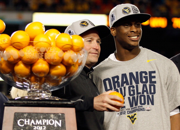 MIAMI GARDENS, FL - JANUARY 04:  (L-R) Head coach Dana Holgorsen and Geno Smith #12 of the West Virginia Mountaineers celebrate with the trophy after they won 70-33 against the Clemson Tigers during the Discover Orange Bowl at Sun Life Stadium on January 4, 2012 in Miami Gardens, Florida.  (Photo by Mike Ehrmann/Getty Images)