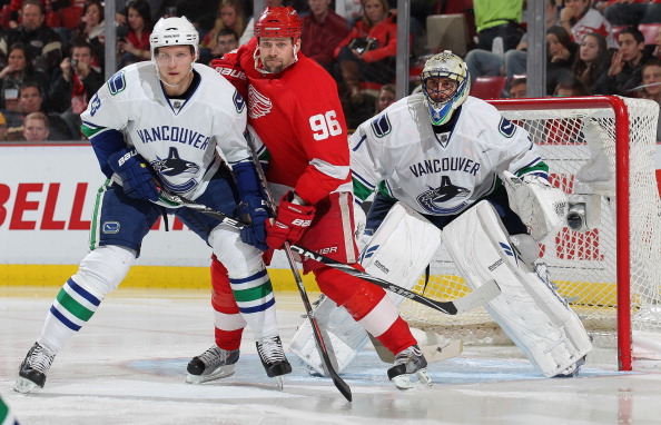 DETROIT, MI - DECEMBER 22:  Tomas Holmstrom #96 of the Detroit Red Wings battles for position between Roberto Luongo #1 and Alexander Edler #23 of the Vancouver Canucks in a game on December 22, 2010 at the Joe Louis Arena in Detroit, Michigan. The Wings defeated the Canucks 5-4 in overtime. (Photo by Claus Andersen/Getty Images)