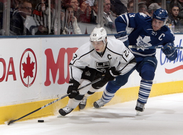TORONTO, CANADA - DECEMBER 19: Dion Phaneuf #3 of the Toronto Maple Leafs cross checks Dustin Brown #23 of the Los Angeles Kings during NHL action at The Air Canada Centre December 19, 2011 in Toronto, Ontario, Canada. (Photo by Abelimages/Getty Images)