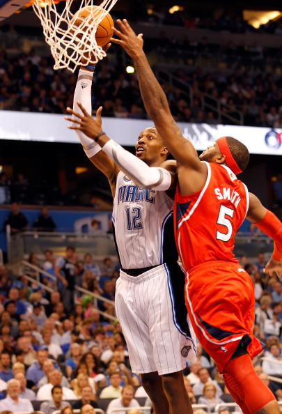 ORLANDO, FL - APRIL 16:  Dwight Howard #12 of the Orlando Magic shoots over Josh Smith #5 of the Atlanta Hawks during Game One of the Eastern Conference Quarterfinals of the 2011 NBA Playoffs on April 16, 2011 at the Amway Arena in Orlando, Florida.  NOTE TO USER: User expressly acknowledges and agrees that, by downloading and/or using this Photograph, user is consenting to the terms and conditions of the Getty Images License Agreement.  (Photo by J. Meric/Getty Images)