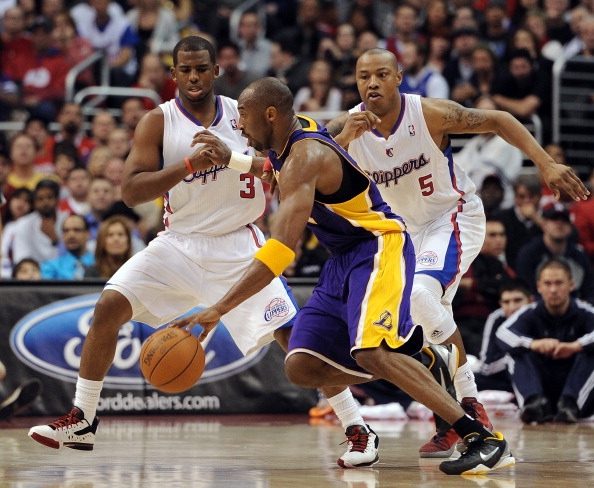 LOS ANGELES, CA - JANUARY 14:  Kobe Bryant #24 of the Los Angeles Lakers is guarded by Chris Paul #3 and Caron Butler #5 of the Los Angeles Clippers during a 102-94 Clipper win at Staples Center on January 14, 2012 in Los Angeles, California.  NOTE TO USER: User expressly acknowledges and agrees that, by downloading and/or using this Photograph, user is consenting to the terms and conditions of the Getty Images License Agreement.  (Photo by Harry How/Getty Images)