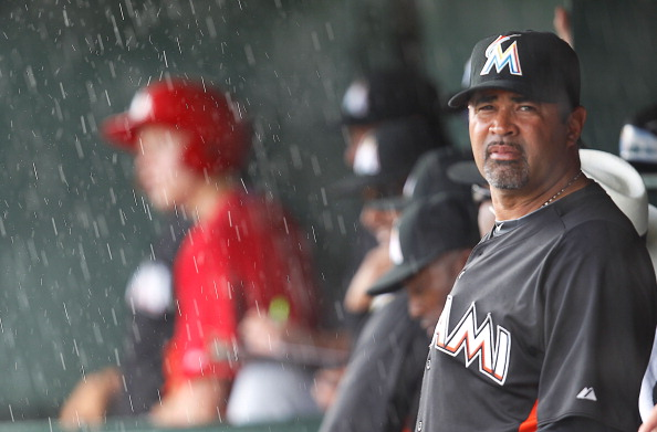 JUPITER, FL - MARCH 18:  Manager Ozzie Guillen #13 of the Miami Marlins takes shelter from the rain during a game against the St. Louis Cardinals at Roger Dean Stadium on March 18, 2012 in Jupiter, Florida.  (Photo by Sarah Glenn/Getty Images)