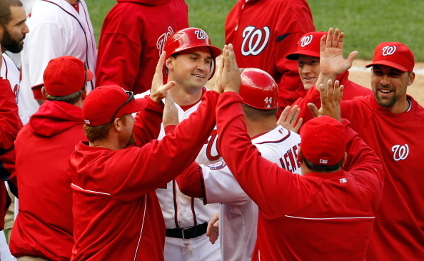 WASHINGTON, DC - APRIL 12: Ryan Zimmerman #11 of the Washington Nationals (C) celeberates after scoring the game winning run on a wild pitch to give the Nationals a 3-2 win over the Cincinnati Reds in the tenth inning during opening day at Nationals Park on April 12, 2012 in Washington, DC.  (Photo by Rob Carr/Getty Images)