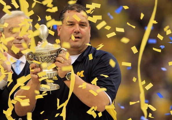 NEW ORLEANS, LA - JANUARY 03:  Head coach Brady Hoke of the Michigan Wolverines celebrates with the trophy after Michigan won 23-20 in overtime against the Virginia Tech Hokies during the Allstate Sugar Bowl at Mercedes-Benz Superdome on January 3, 2012 in New Orleans, Louisiana.  (Photo by Matthew Stockman/Getty Images)