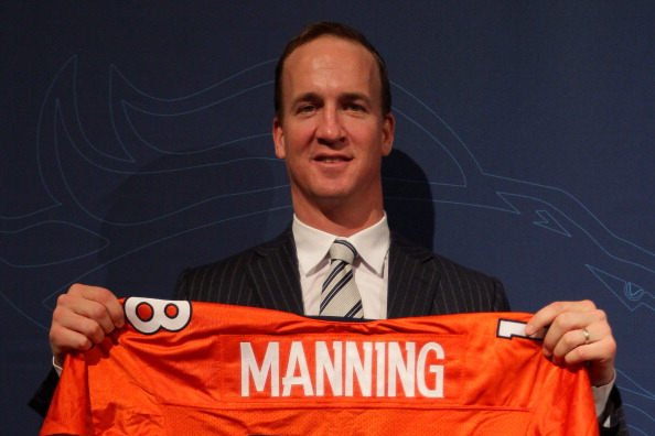 ENGLEWOOD, CO - MARCH 20:  Quarterback Peyton Manning poses with his uniform after the news conference announcing his contract with the Denver Broncos in the team meeting room at the Paul D. Bowlen Memorial Broncos Centre on March 20, 2012 in Englewood, Colorado. Manning, entering his 15th NFL season, was released by the Indianapolis Colts on March 7, 2012, where he had played his whole career. It has been reported that Manning will sign a five-year, $96 million offer.  (Photo by Doug Pensinger/Getty Images)
