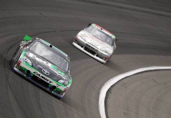 KANSAS CITY, KS - APRIL 22:  Denny Hamlin, driver of the #11 FedEx Ground Toyota, leads Dale Earnhardt Jr., driver of the #88 Diet Mountain Dew/National Guard Chevrolet, during the NASCAR Sprint Cup Series STP 400 at Kansas Speedway on April 22, 2012 in Kansas City, Kansas.  (Photo by Jamie Squire/Getty Images)