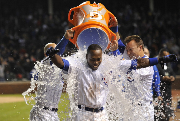 CHICAGO, IL - APRIL 24:   Alfonso Soriano #12 of the Chicago Cubs receives a Gatorade bath from teammates Reed Johnson #5 (L) and Jeff Baker #3 after hitting a game-winning RBI single scoring Tony Campana #1 during the 10th inning against the St. Louis Cardinals at Wrigley Field on April 24, 2012 in Chicago, Illinois. The Cubs defeated the Cardinals 3-2 in 10 innings.  (Photo by Brian Kersey/Getty Images)