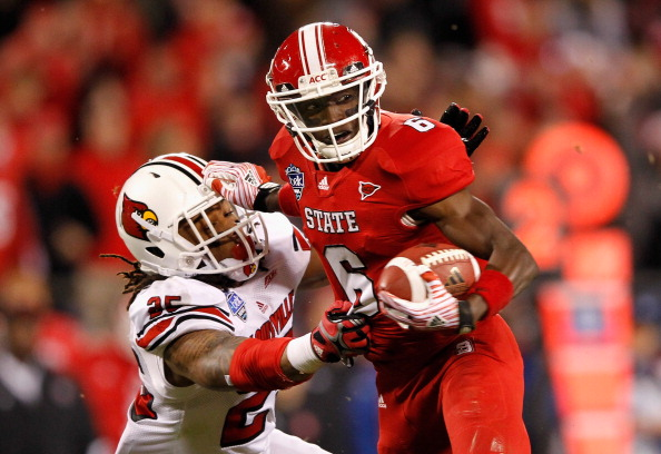 CHARLOTTE, NC - DECEMBER 27:  T.J. Graham #6 of the North Carolina State Wolfpack gets away from Anthony Branch #25 of the Louisville Cardinals on his way to scoring a touchdown during their game at Bank of America Stadium on December 27, 2011 in Charlotte, North Carolina.  (Photo by Streeter Lecka/Getty Images)