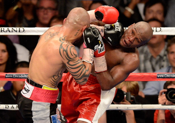 LAS VEGAS, NV - MAY 05:  Miguel Cotto (L) hits Floyd Mayweather Jr. during the ninth round of their WBA super welterweight title fight at the MGM Grand Garden Arena May 5, 2012 in Las Vegas, Nevada. Mayweather won by unanimous decision.  (Photo by Ethan Miller/Getty Images)