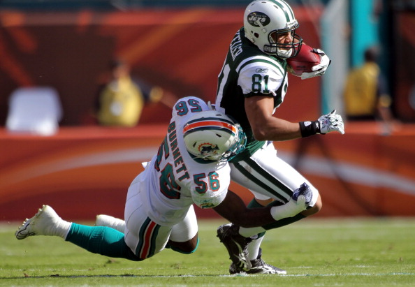 MIAMI GARDENS, FL - JANUARY 01:  Tight end Dustin Keller #81 of the New York Jets is brought down by Linebacker Kevin Burnett #56 of the Miami Dolphins at Sun Life Stadium on January 1, 2012 in Miami Gardens, Florida.  (Photo by Marc Serota/Getty Images)