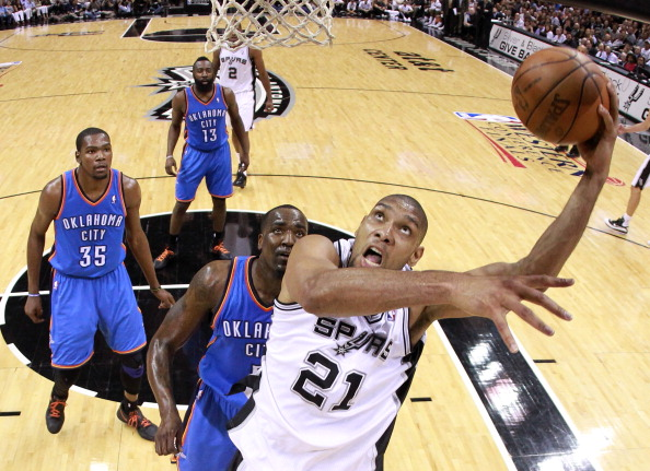 SAN ANTONIO, TX - MAY 27:  Tim Duncan #21 of the San Antonio Spurs lays the ball up in front of Kendrick Perkins #5 of the Oklahoma City Thunder in the second half in Game One of the Western Conference Finals of the 2012 NBA Playoffs at AT&T Center on May 27, 2012 in San Antonio, Texas. NOTE TO USER: User expressly acknowledges and agrees that, by downloading and or using this photograph, user is consenting to the terms and conditions of the Getty Images License Agreement.  ((Photo by Ronald Martinez/Getty Images)