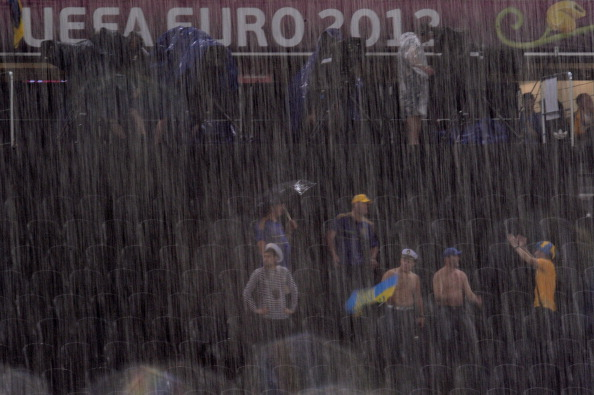 DONETSK, UKRAINE - JUNE 15:  Football fans shelter from the rain during the UEFA EURO 2012 group D match between Ukraine and France at Donbass Arena on June 15, 2012 in Donetsk, Ukraine.  (Photo by Lars Baron/Getty Images)