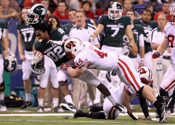 INDIANAPOLIS, IN - DECEMBER 03:  Keshawn Martin #82 of the Michigan State Spartans loses his helmet as he is hit by Chris Borland #44 of the Wisconsin Badgers during the third quarter of the Big 10 Conference Championship Game at Lucas Oil Stadium on December 3, 2011 in Indianapolis, Indiana.  (Photo by Andy Lyons/Getty Images)