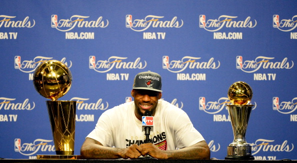 MIAMI, FL - JUNE 21:  LeBron James #6 of the Miami Heat answers questions from the media next to the Larry O'Brien Finals Championship trophy and James' Bill Russell Finals MVP trophy during his post game press conference after they won 121-106 against the Oklahoma City Thunder in Game Five of the 2012 NBA Finals on June 21, 2012 at American Airlines Arena in Miami, Florida. NOTE TO USER: User expressly acknowledges and agrees that, by downloading and or using this photograph, User is consenting to the terms and conditions of the Getty Images License Agreement.  (Photo by Ronald Martinez/Getty Images)