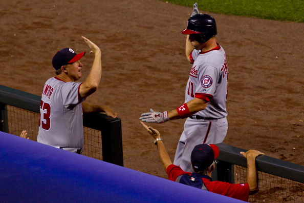 DENVER, CO - JUNE 26:  Ryan Zimmerman #11 of the Washington Nationals is greeted at the dugout by coach Randy Knorr (L) after hitting a home run against the Colorado Rockies at Coors Field on June 26, 2012 in Denver, Colorado.  The Nationals defeated the Rockies 12-5.  (Photo by Justin Edmonds/Getty Images)