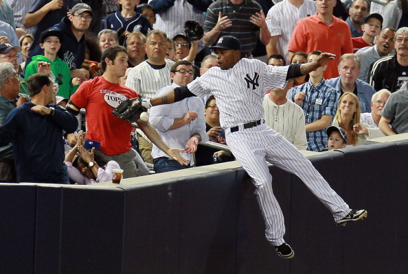 NEW YORK, NY - JUNE 26:  Dewayne Wise #45 of the New York Yankees falls into the stands after making a catch off the bat of Jack Hannahan #9 of the Cleveland Indians in the seventh-inning at Yankee Stadium on June 26, 2012 in the Bronx borough of New York City.  (Photo by Mike Stobe/Getty Images)